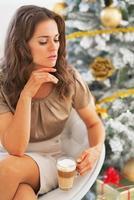 retrato de mulher jovem com latte macchiato perto da árvore de Natal foto