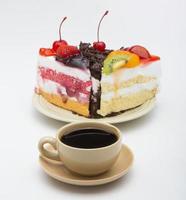 xícara de café e bolo delicioso no fundo branco foto