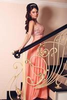 linda noiva em elegante vestido coral posando na escada foto