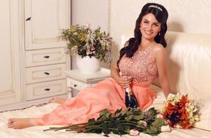 Noiva linda e sorridente segurando uma garrafa de champanhe foto