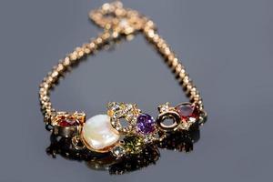 pulseira de ouro com pedras preciosas em fundo cinza