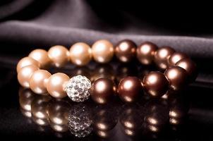 linda pulseira de pérolas em fundo preto foto