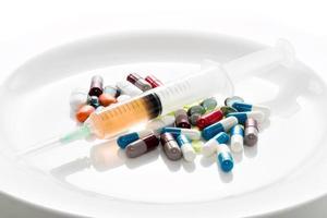 tabletten und spritze auf einem teller foto