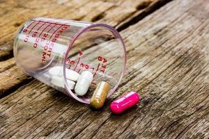 comprimidos derramando na velha mesa de madeira foto
