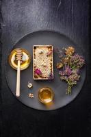 mel e ervas secas em fundo escuro