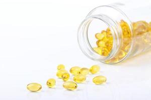 cápsulas de vitamina derramadas da garrafa foto