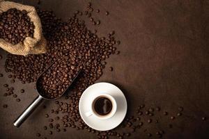 xícara de café e colher em fundo marrom foto