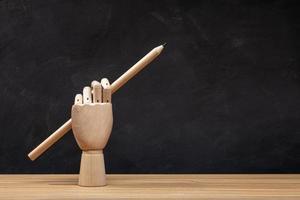 mão de madeira segurando um lápis