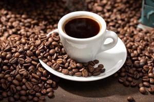 xícara de café expresso e grãos torrados foto