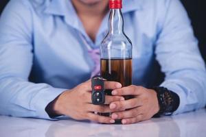homem com uma garrafa de cerveja e a chave do carro foto