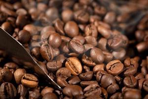 close up de grãos de café torrados e colher foto