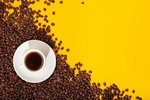 xícara de café e grãos torrados em fundo amarelo foto