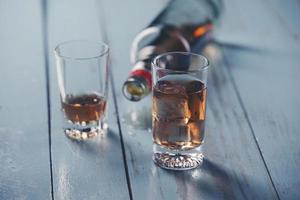 copos e uma garrafa de álcool foto
