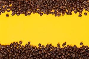 grãos de café em fundo amarelo foto