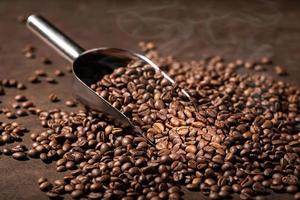 fundo do café. grãos de café torrados e colher foto