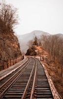 trilhos de trem entre colinas rochosas foto