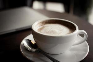 close-up de café com leite e laptop na mesa foto