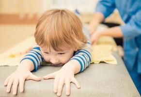 garotinho na mesa de massagem foto