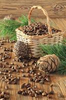 nozes de cedro em uma cesta de vime em uma mesa de madeira foto
