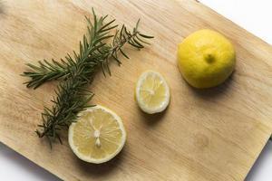 alecrim e limão na tábua de cortar foto