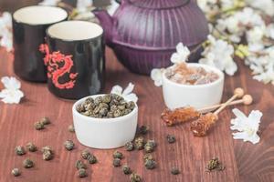 Jogo de chá asiático com chá verde seco e açúcar foto