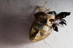 máscaras venezianas em parede velha foto