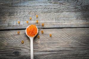 colher de caviar vermelho no fundo de madeira foto