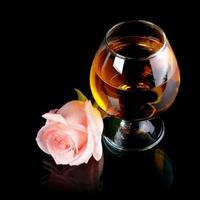 copo com álcool e rosa. foto