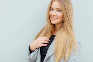 mulher de cabelo loiro andando na rua e sorrir foto