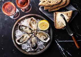 ostras abertas, pão com manteiga e vinho rosé foto