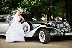 noiva luxuosa em um vestido de noiva sobre limusine retrô