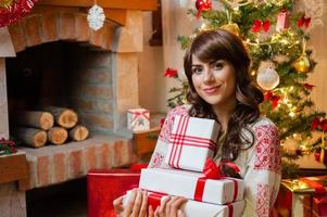 jovem com caixas de presentes de natal foto