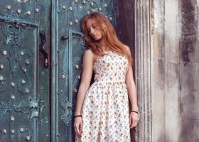 garota ruiva da moda em pé perto de uma parede azul foto