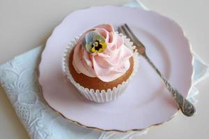 cupcakes caseiros de baunilha com cobertura rosa e flores comestíveis foto