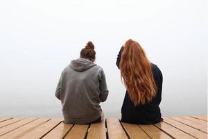 duas mulheres sentadas em um píer de madeira