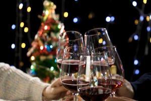 pessoas tilintando taças de vinho em comemoração