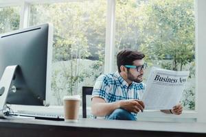 homem caucasiano lendo notícias de negócios