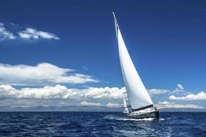 Navegando. enviar iates com velas brancas em mar aberto.