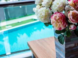 flores artificiais com vaso rústico de madeira perto da piscina
