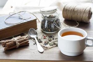xícara de chá quente com livros, folhas de chá e flores foto