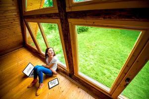 mulher sentada no chão em casa de madeira