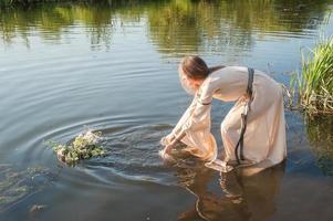 linda garota abaixa coroa na água foto