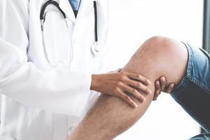 médico verificando joelhos do paciente