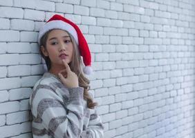 mulher com chapéu de Papai Noel encostado na parede