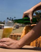 derramando cerveja na praia
