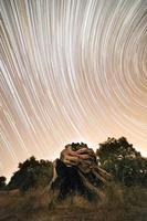 lapso de tempo de estrelas acima de uma formação rochosa foto