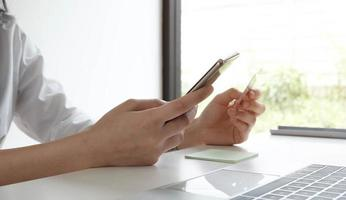 mulher segurando smartphone e cartão de crédito foto