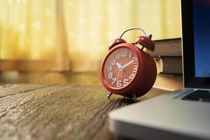 relógio vermelho vintage e laptop na mesa de madeira