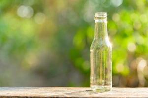 uma garrafa de vidro vazia colocada sobre uma mesa de madeira foto