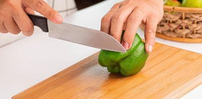 close-up de uma pessoa cortando um pimentão foto